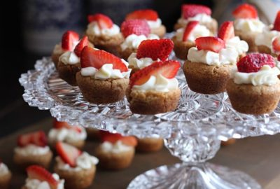 A glass tray filled with little sponge cake smothered in cream and topped with a strawberry.