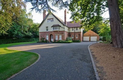View from the gate of a large home with tarmac driveways leading to the door